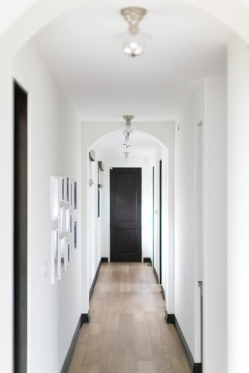 Long white and black hallway boasts arched doorways illuminated by nickel and glass flush mount lights hung above a wood floor lined with black baseboards.