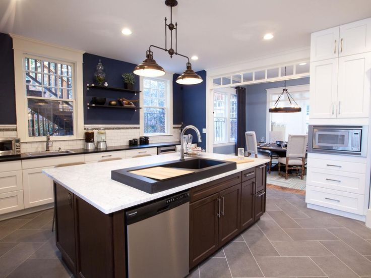 This kitchen, seen on HGTV's Property Brothers, was enlarged by taking down the wall between the pantry and dining room. The kitchen is painted navy blue with white cabinets and a dark-stained wood island.