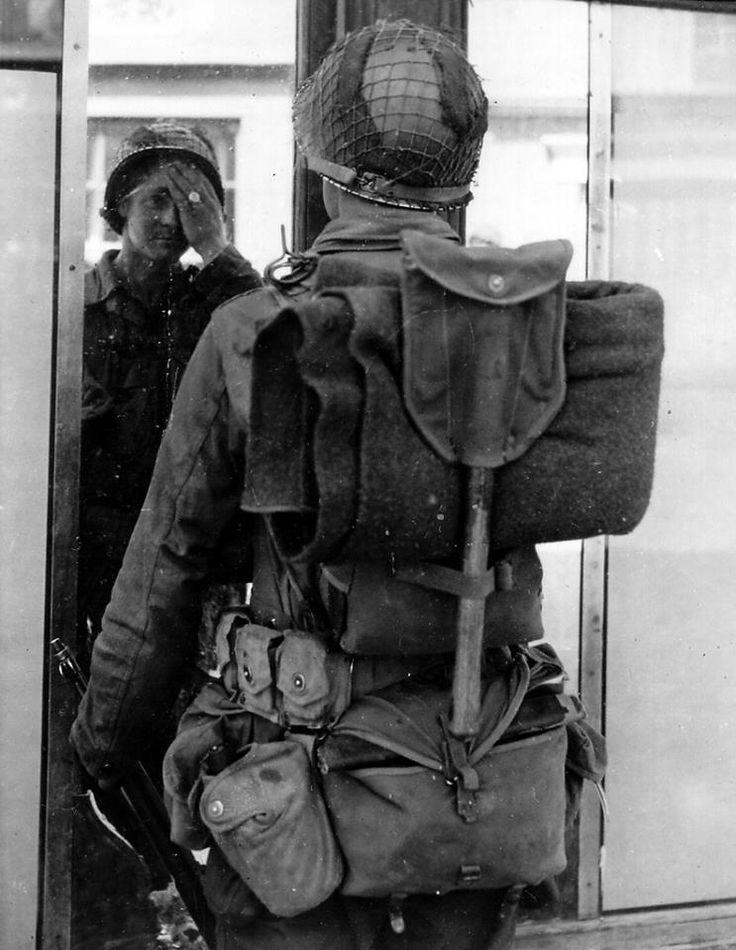 """Private Vincent Kamolz, voltigeur au 26th Regiment de la lst Infantry Division. """"Je me souviens qu'il faisait très chaud et que je me suis trouvé face à cette glace dans la rue. Alors que je m'y regardais. J'ai appris plus tard par ma famille que cette photo avait été publiée dans les journaux"""". Kamolz ne se souvient pas du tout de son gilet d'assaut. Il appartient au régiment de seconde vague de la Big Red One, c'est possible qu'il l'ait récupéré d'un homme hors de combat."""