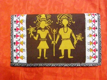 """An eco-friendly jute purse (10"""" x 6"""") with motifs from the Warli paintings of Maharashtra. The warli designs are hand-painted with fabric colours and will be water-resistant. The purse backgrounds are white (near borders) and cocoa brown (center), the tarpa dance borders in yellow ochre and fuchsia pink, the central motifs in yellow ochre."""