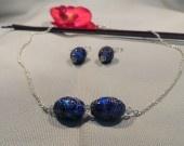 Très belle parure épuré comprenant un collier, en chaîne argent agrémenté de perles cloisonnées bleus et de cristal de swarovski, et de boucles d'oreille ornées de cristal de swarovki blanc et de perles cloisonnées bleu