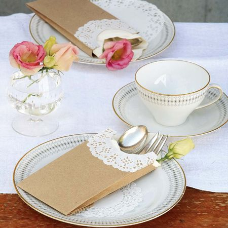Make a delicate cutlery holder using plain, brown paper packets and a paper doily. The doily adds a lace-like trim that turns something inexpensive into an attractive finishing touch for a special table setting.