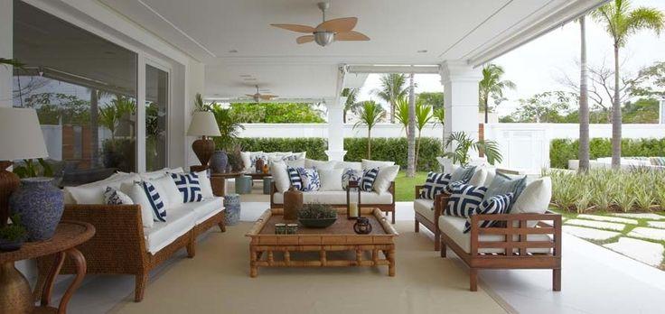 Projeto de Adriana Bijara Cuoco na casa de praia , com moveis de madeira e estofados em branco e azul mais ventolador de teto e abajur
