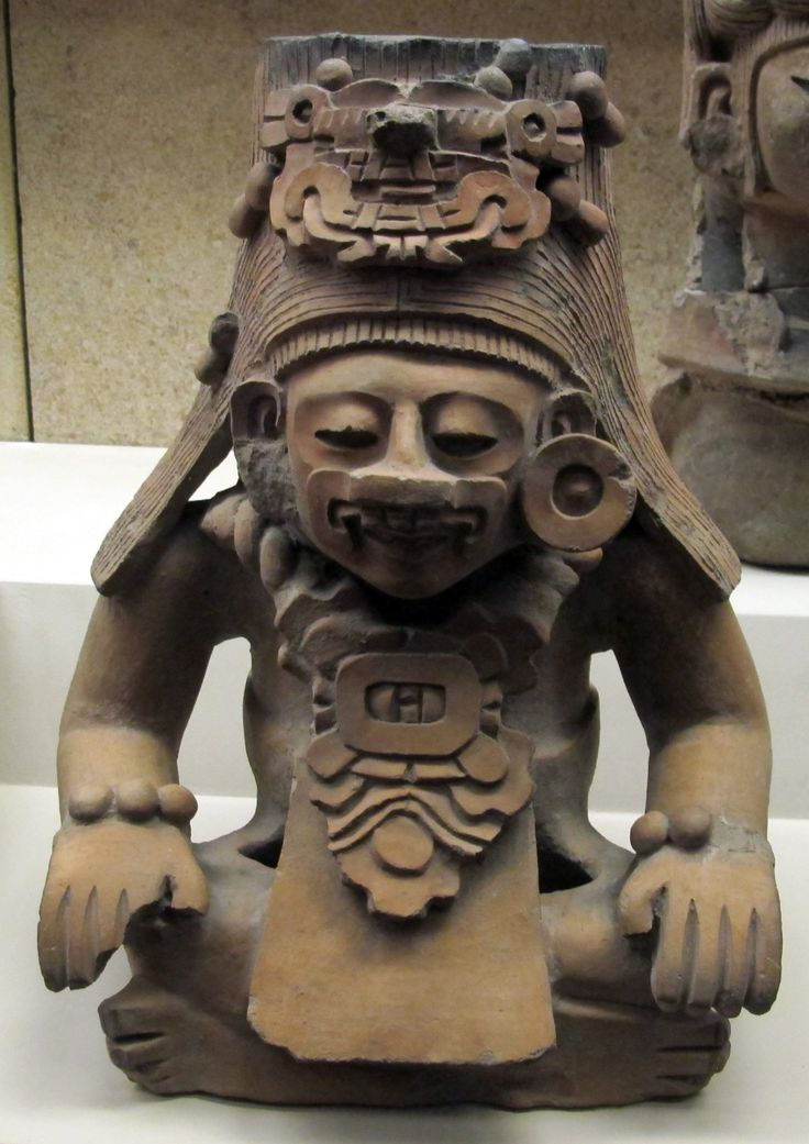 Pottery ancestor figure,Zapotec, 200 BC - AD 800.From the Oaxaca Valley, Mexico.  The figure on this example wears a mask and headdress representing the depicted ancestors' potent supernatural force. The chest ornament features a glyph or sculpted symbol of a day in the 260-day Zapotec ritual calendar. The exact use and purpose of these vessels is unknown. The container, or urn, itself - usually a cylindrical vessel hidden behind the sculpted figure -