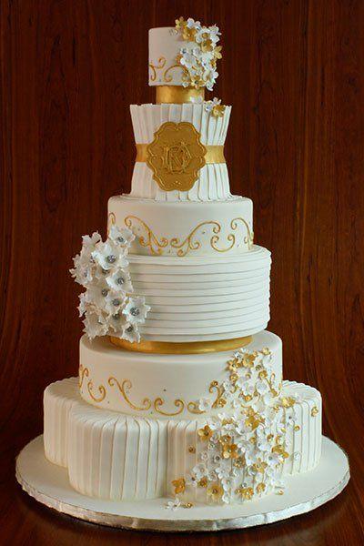 Combine formas únicas, como uma base floral e uma camada de cinto acentuada por um monograma, com toques de ouro brilhantes e abundância de textura.Bolo por Elegantemente Iced
