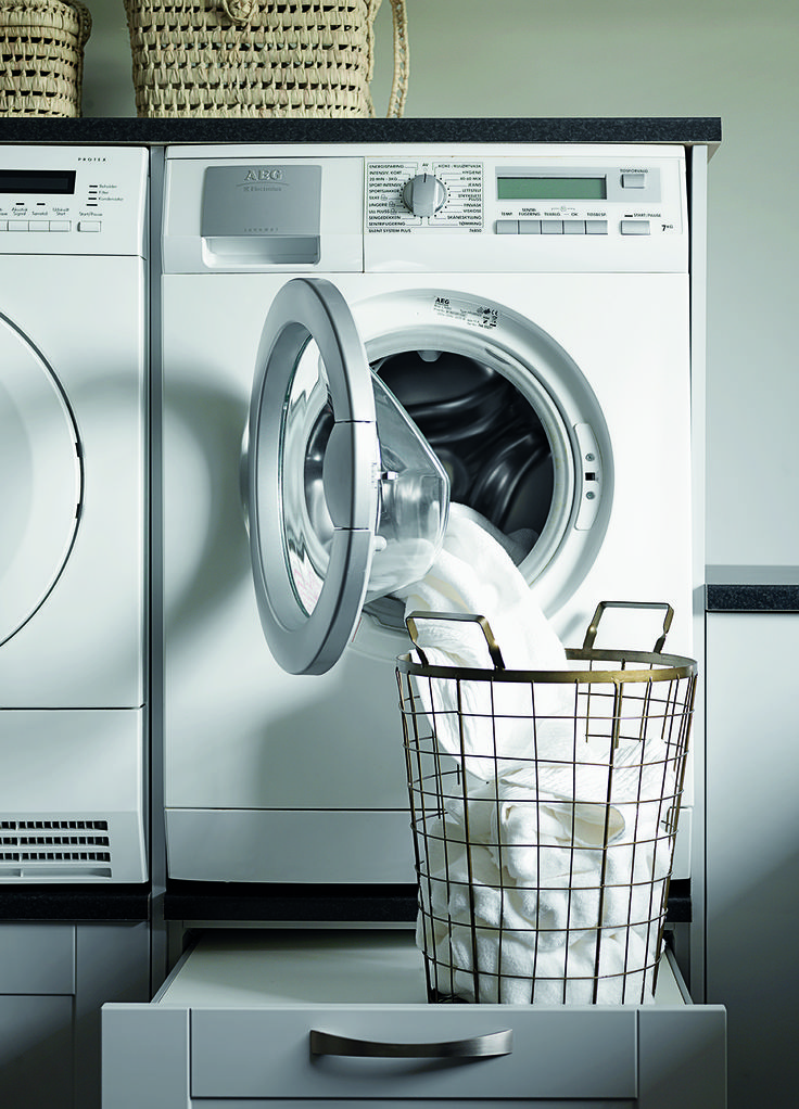 Vaskemaskine og tørretumbler er hævet til ergonomisk korrekt højde, og skuffen nedenunder har en smart udtræksplade til vasketøjskurven.