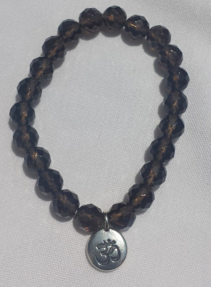 Faceted Smoky Quartz Mala with OM charm $45. Smoky quartz used to disperse negativity in the wearers mind and environment. It is a grounding stone that focuses on the base and solar plexus chakras for the wearer.