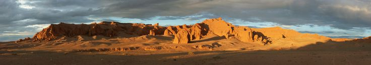 """https://flic.kr/p/o82VSe   Flaming Cliffs   Flaming Cliffs. This area of the Gobi desert is most famous for the first nest of dinosaur eggs and other fossils found here by the American paleontologist Roy Chapman Andrews in the 1920s. He nicknamed this site """"Flaming Cliffs"""" for the surreal glowing orange color of the rock. Called Bayanzag in Mongolian, which means """"rich in saxaul shrubs"""", it is comprised of red sand, rocks, scorching sun, and emptiness."""