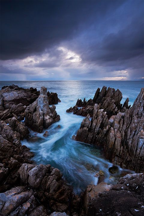 landscape photograph of waves rushing onto the rocks on the gansbaai coasltine below a dramatic sunset