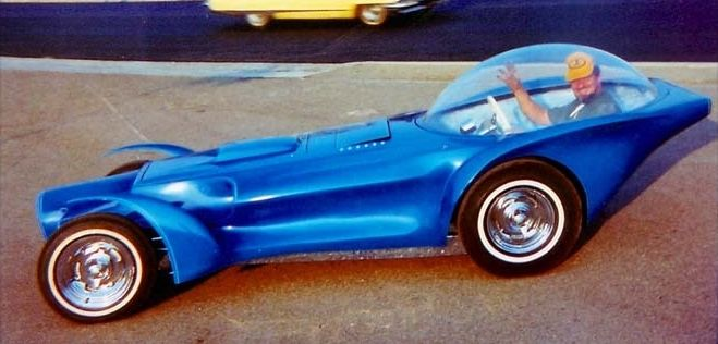 "Ed Roth inside his ""Orbitron"" custom car, an asymmetrical design created in 1964. Orbitron featured three primary colored headlights, which in theory when illuminated concurrently would blend into a white beam."