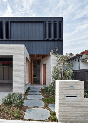 From the street, the new house presents itself as stacked cubic forms.