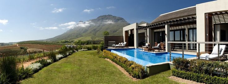 Scenic Estate in South African Wine Country has a wood paneled deck, an infinity pool, elegant lounge furniture, a trellis, folding shutters, and a beautiful view of the vineyards.