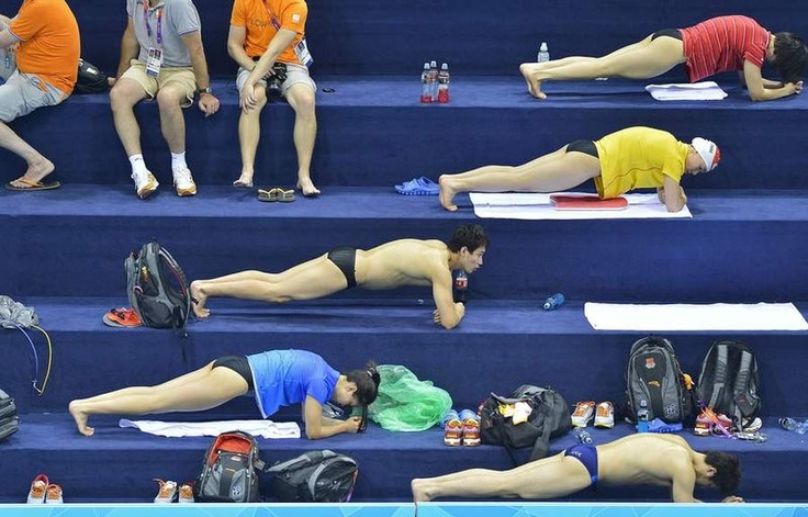 Chinese zwemmers zijn bezig met hun rek- en strekoefeningen in het Aquatics Centre op het Olympisch Park. Met nederlandse vertegenwoordigers op de achtergrond ;-) © reuters