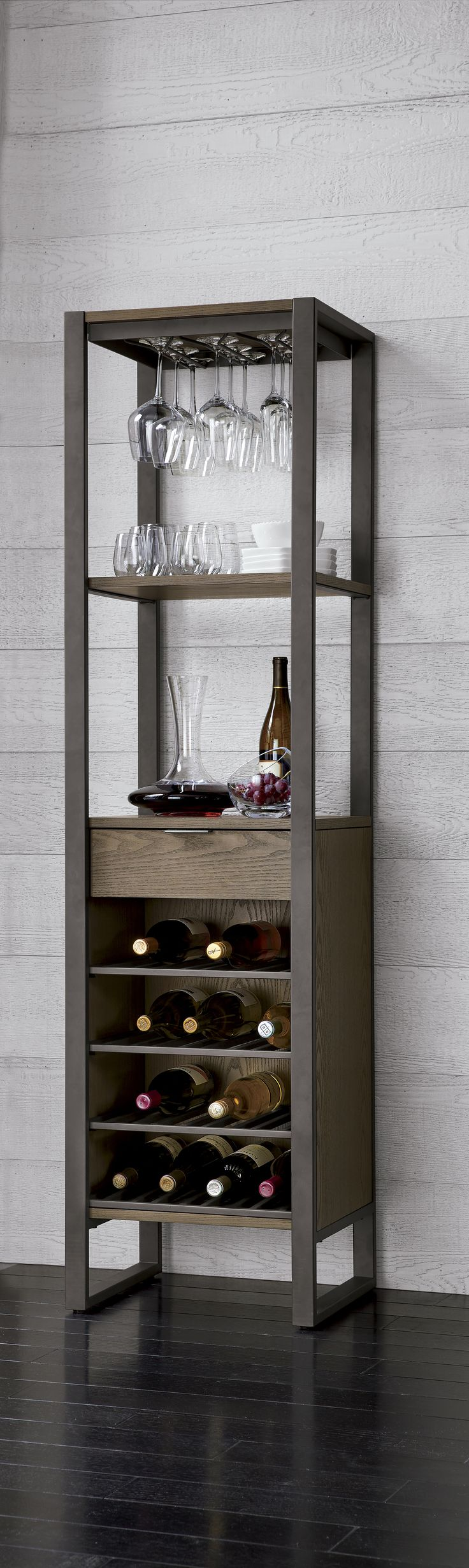 This all-in-one wine tower promises to be the center of the party. Crafted of ash veneer with a warm charcoal finish, this tall storage piece provides airy and open shelves to rack stemware and provide easy access to barware and bottles. A drawer at midpoint keeps recipes and bar tools tucked away, while down below, a wine grid stows up to 16 bottles.