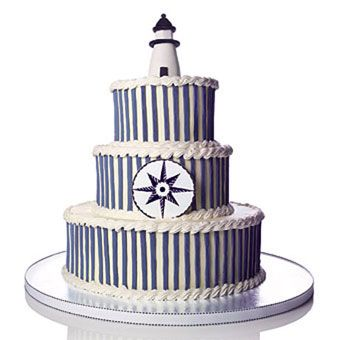 Lemon cake filled with three-berry compote is covered with blue fondant stripes, and accented with a tiny sugar lighthouse and compass to really drive home the nautical theme. Cake by Gail Watson