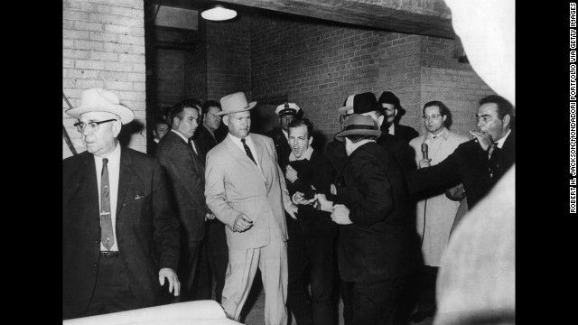 Two days after President John F. Kennedy was killed in 1963, Dallas nightclub owner Jack Ruby gunned down Lee Harvey Oswald, the alleged assassin. Photographer Robert H. Jackson, who covered the event's surrounding Kennedy's assassination, instinctively captured the moment and won a Pulitzer Prize. Ruby was later found guilty of murder. He appealed his conviction but died before the start of a new trial.