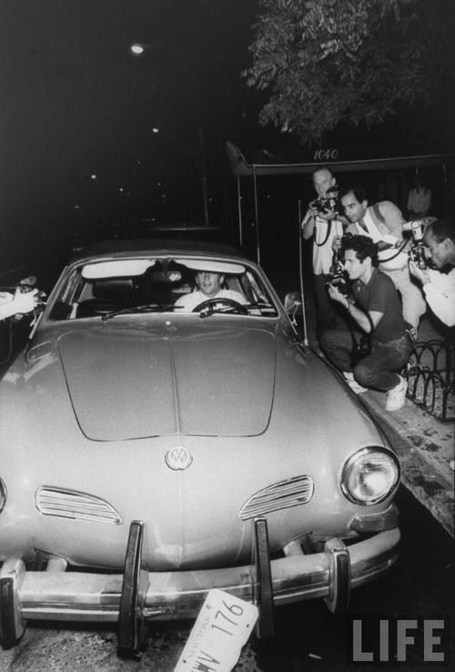 John F. Kennedy, Jr., arriving for his aunt Lee Radziwill's wedding to Herbert Ross in his Volkswagen Karman Ghia, is surrounded by photographers, 9/24/88, New York, NY.