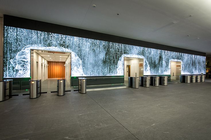 "San Francisco-based studio Obscura was commissioned by Salesforce to create this gigantic LED video wall installation for the lobby of their flagship office.   ""Our creative teams worked closely together to envision and produce work that transforms a passageway into a mesmerizing hyperreal environment. From capturing California's Redwood National Forest in stunning 12K resolution, to a designing a convincing CG waterwall and more – we held nothing back in striving to impart a sense of wo..."