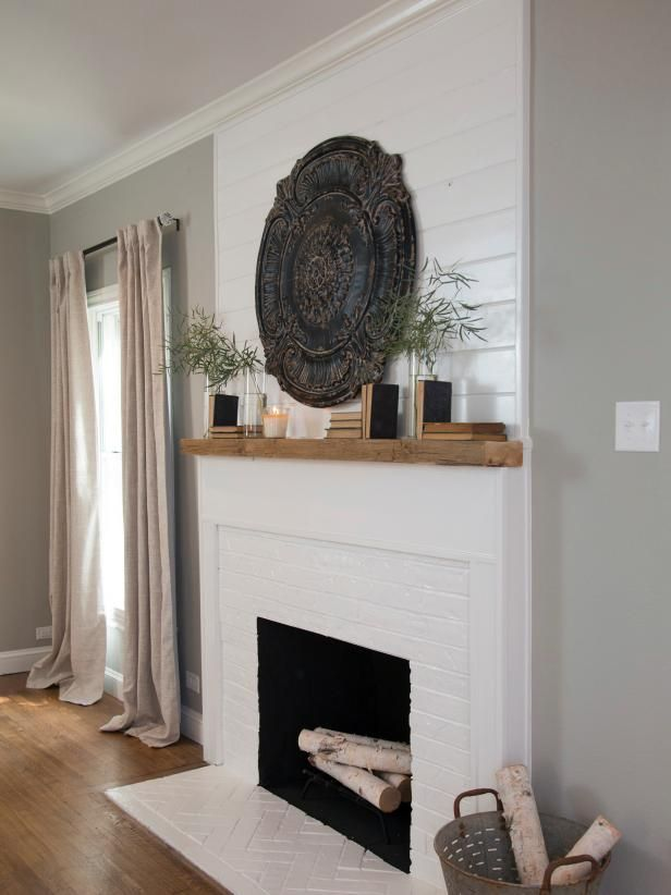 The original fireplace brick was painted white and shiplap paneling with a natural wood mantle was installed. The living room is staged with French Country  accessories, books, and bright linen window treatments, as seen on HGTV's Fixer Upper.