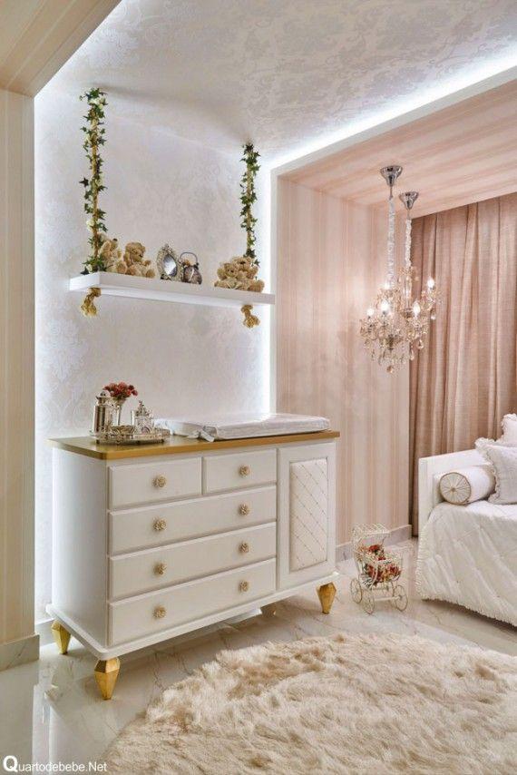 Nicho preso por cordas envolta por plantas penduradas no teto. A decoração também conta com uma cômoda branca com bancada, pés e puxadores dourados.