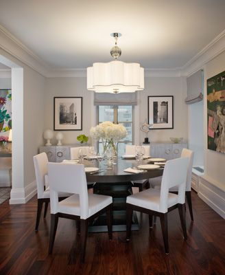 I love this for several reasons. The dark floors with withe trim. The fabric chairs. The hydrangeas, the lighting, the round table makes everyone at the table equally as important...love it all.