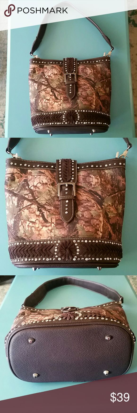"""Montana West Camo Concealed Handgun Purse Gorgeous Montana West Camo Concealed Handgun Purse. Camouflage colors. Magnetic buckle closure, camo material on front & back of purse with lots of silver stud & faux diamond bling! Has open pocket on back of purse with zipper concealed handgun pocket. Inside has two large compartments with zipper pocket in middle, open pockets on one side & zipper pocket on opposite side. Lots of room for all of your essentials and more. Shoulder strap has 12"""" drop…"""