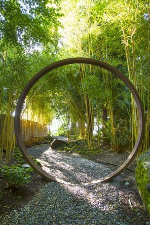 Visitors enter the garden along a shady gravel path, stepping through a moon gate designed and installed by Terry Welch.