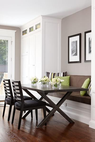 A built-in banquette flanked by tall pantry cabinets creates an eating nook. Dark-stained oak floors help warm up the white cabinetry. | Photo: Stacey Brandford | thisoldhouse.com