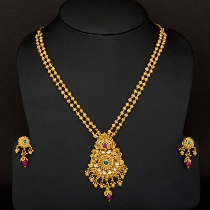 two layer gundla mala chains attached to large antique gold pendant having small gold ball hangings. The pedant is further beautified with color stones. It comes along with small ear studs