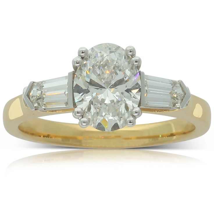 18ct yellow and 18ct white gold 1.30ct diamond ring This breathtaking 18ct yellow and white gold setting holds a spectacular oval cut centre diamond with a tapered cut diamond on either side. This exquisite ring was made to impress!
