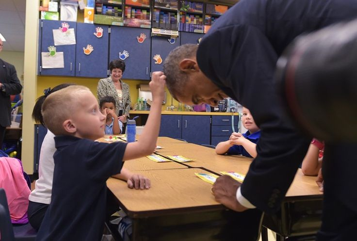 US President Barack Obama leans over so a little boy can feel his hair during a visit to a primary school at MacDill Air Force Base in Tampa, Florida
