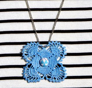 Romantic necklace made from crochet painted metallic light blue and decorated with a unique vintage fabric button.With silver plated chain.  Length of chain:38cm Dimensions of crochet part:6cm*6cm