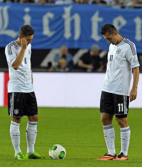 Mesut Özil and Miroslav Klose. Hmm,  a ball... What should we do with it? Maybe we should kick it!