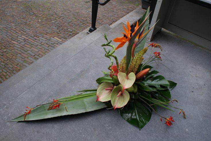 Verbondenheid, basis met blad bekleed. Bloemwerk van Bloematelier Fleur & Geur. Tropische combinatie