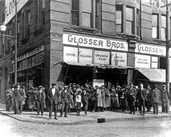 black and white photo of corner of Glosser Brothers store, store windows advertise items for sale, corner of sidewalk is crowded with people