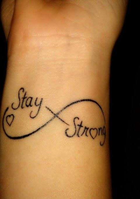 "Little wrist tattoo saying ""Stay strong"" with a heart and a infinity symbol."