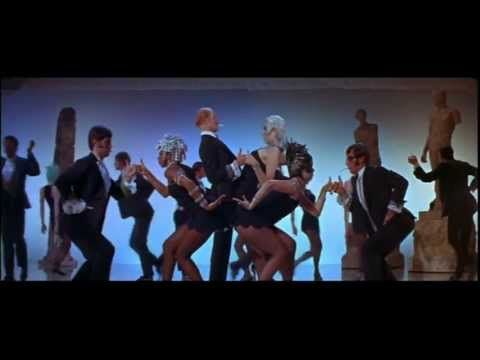 """The Rich Man's Frug"", a wildly energetic1960s  dance number comprising three ""movements"" (""The Aloof"", ""The Heavyweight"" and ""The Big Finish"") that showcases director Bob Fosse's distinctive choreography style, particularly his creative use of unusual poses, gestures, and arm movement.  The styling is amazing!!!"
