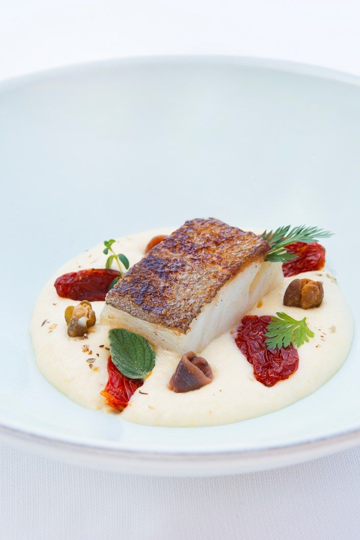 Pan-fried cod fillet with polenta mousse, anchovies, fried capers and candied tomatoes
