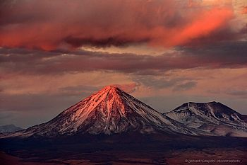 Snow covered volcanoes Licancabur and Juriques in a dramatic sunset, San Pedro de Atacama