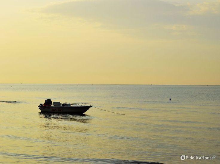 Un motoscafo è ormeggiato a pochi passi dalla riva, pronto per partire per il…