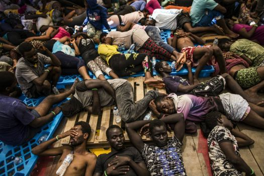"""...and who can say: Do not Enter!...""""Mediterranean Sea  Migrants from Nigeria and Ivory Coast rest after being rescued by a migrant offshore aid station team in the Mediterranean, close to Libyan territorial waters. Most of the estimated 94,000 people who have arrived in Italy by boat this year travelled from sub-Saharan Africa to Libya, where people smugglers charge hundreds of dollars for the passage, often in unseaworthy boats.""""   Courtesy of Guardian News & Media Ltd"""