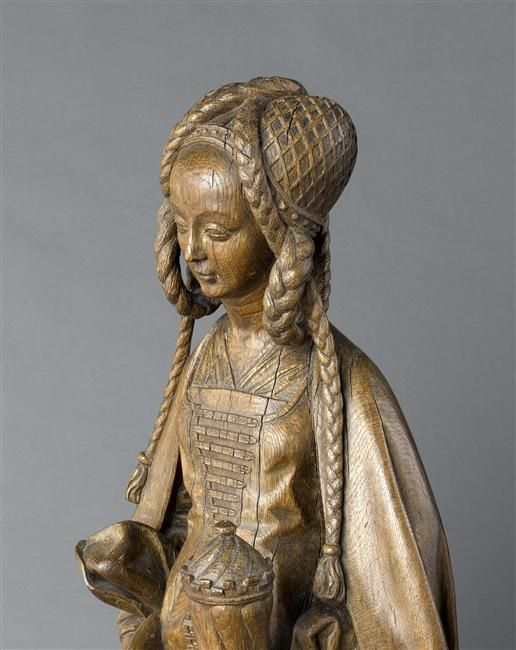 A fifteenth- to sixteenth-century French wooden statue of Saint Mary Magdalene; she holds her symbolic attribute: an ointment pot. Musée National du Moyen-Age.
