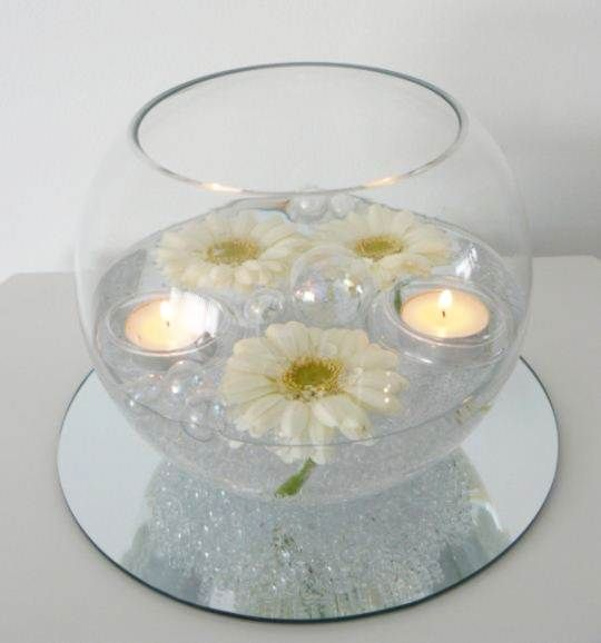 Floating candle in fishbowls with pearls and flower petals. Replace daisies with roses
