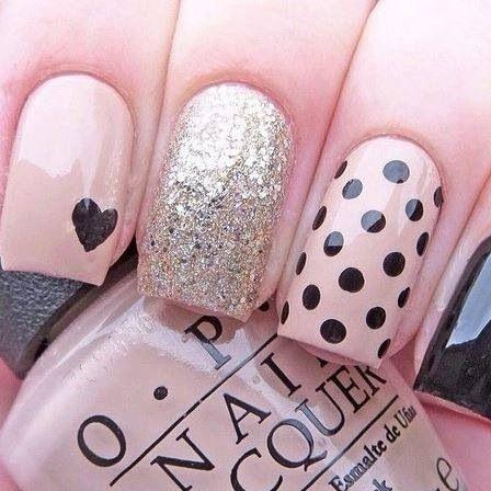 Hermosas uñas en beige, negro y con brillos, algunas de ellas adornadas con lunares negros, otra con un corazón negro en una esquina de la punta.