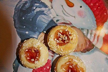 Marzipanbällchen mit Himbeergelee - 200 g Mehl 150 g Marzipan - Rohmasse 1  Ei(er) 50 g Puderzucker 100 g Butter   Aroma (Zitrone), einige Tropfen 1 Glas Konfitüre (Himbeergelee), oder anderes Gelee   Puderzucker zum Bestäuben