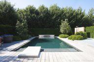 Aanleg betonnen zwembad met springplank, luxe zwembad bekleed met mozaïek