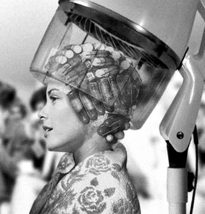 Grace Kelly sits under a hair dryer.