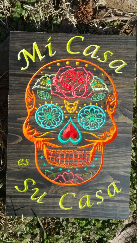 Spanish Welcome Mexican Day of the Dead Decor with Sugar Skull Art Carved & Hand Painted. Measures 12 x 8 Keyhole slot for easy wall mounting.  Welcome friends and loved ones with this vibrantly painted Mexican Day of the Dead Sugar Skull Wall Art! Each Wood Sugar Skull creation is unique, no 2 are the same! Mi Casa es Su Casa means My house is your house a greeting to guests similar to make yourself at home.  The detail and lettering are carved into the wood. The wood is stained Espresso...
