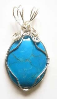Largish turquoise cabochon wrapped with silver plated copper wire and turned into an inexpensive pendant