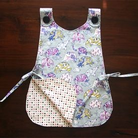 Learn how to make this pinafore-style art smock. It's the perfect gift for any little girl. Downloadable PDF tutorial included!